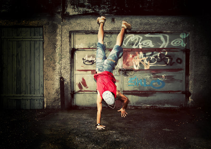 Young man handstands, grunge. Young man jumping / dancing on grunge graffiti wall background royalty free stock photo