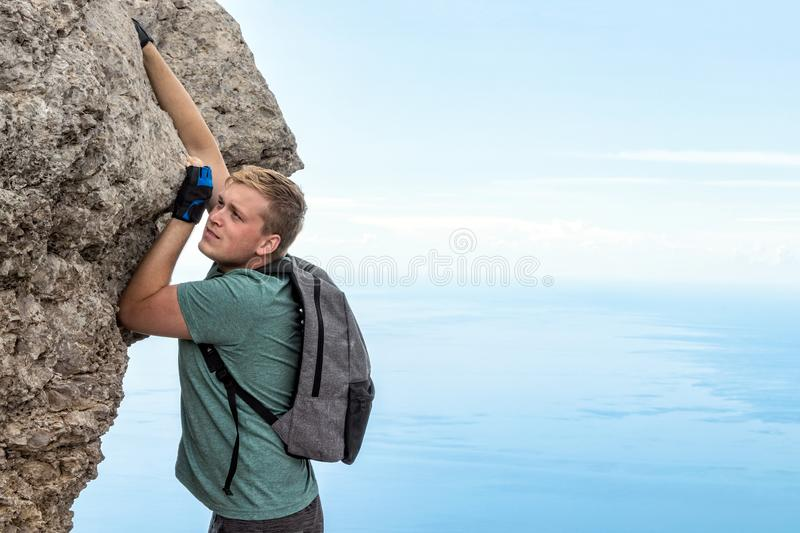 Young man hanging on edge, climbs up the rock royalty free stock photo