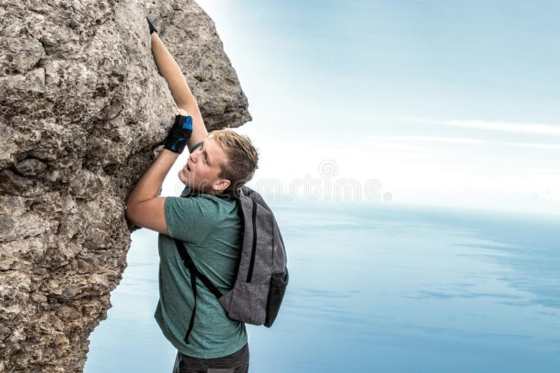 Young man hanging on edge, climbs up the rock royalty free stock images