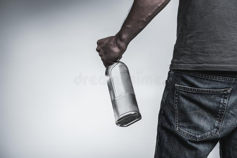Young man has alcohol addiction. Close up of hand of male alcoholic holding bottle of harmful beverage. He is standing and turning back to camera. and copy space stock image