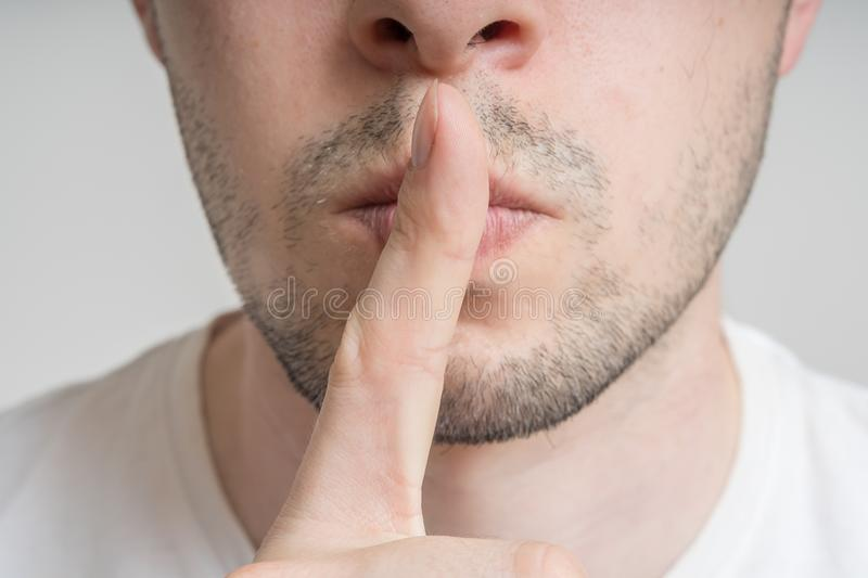 Young man has finger on lips and showing be quiet gesture.  stock photo