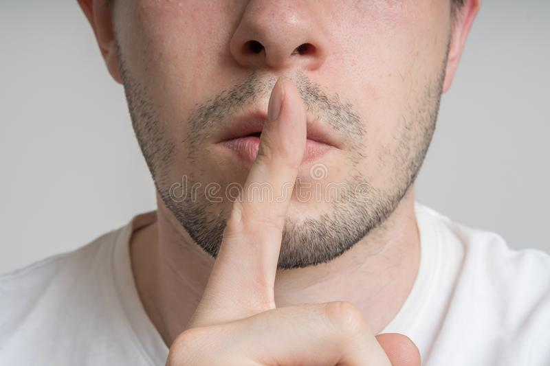 Young man has finger on lips and showing be quiet gesture.  stock images