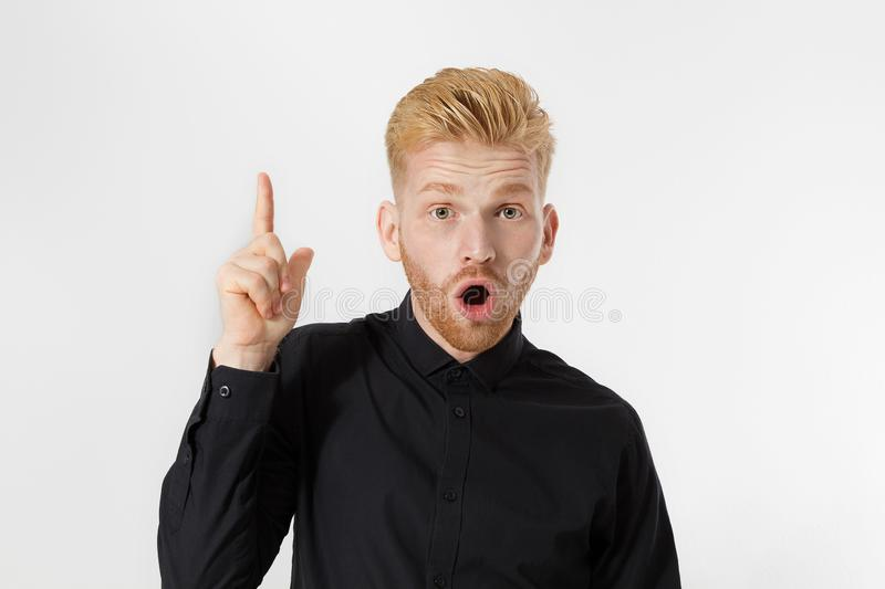 InYoung man has an idea pointg to copy space . Close up redheaded guy with red beard isolated. Shock happy excited male face. royalty free stock photo