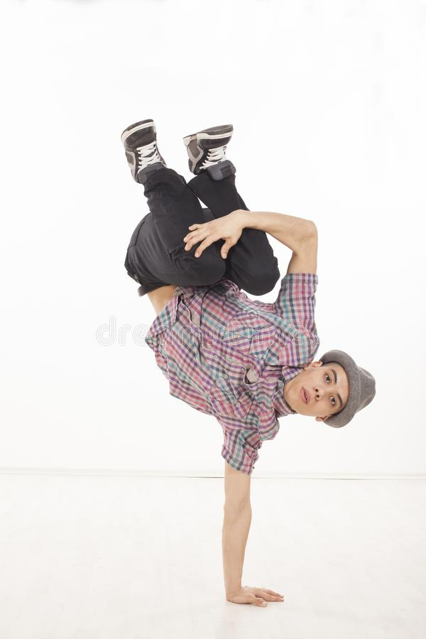 Young man with hat dancing sitting on one hand. Young man wearing casual shirt dancing sitting on one hand, performing breakdance moves on wood floor upside down royalty free stock photography