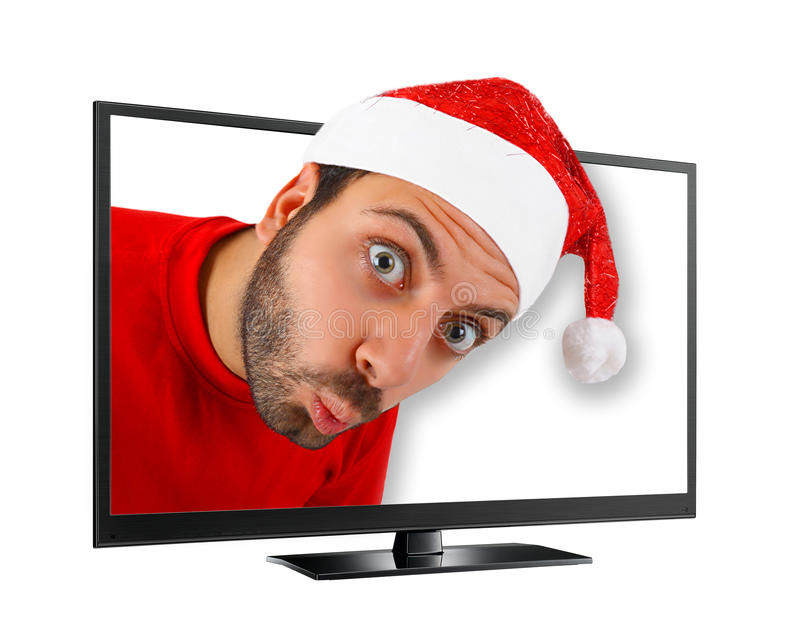 Young man with hat of Santa Claus comes out from the TV. stock photo