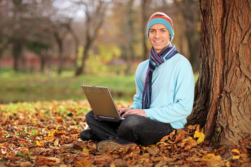 Download Young Man With Hat And Scarf Working On Laptop Stock Photo - Image: 17188652