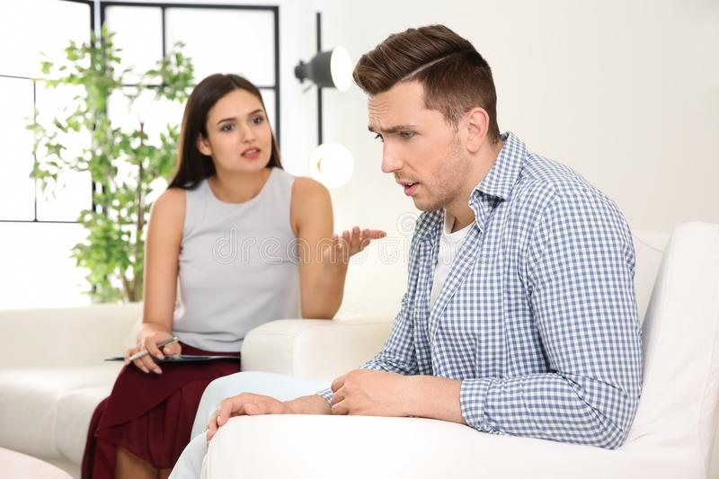 Young man having appointment with psychologist in office. Depressed young men having appointment with psychologist in office stock photos