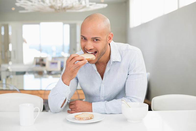 Young man having breakfast at home. Portrait of a handsome young man having breakfast at home royalty free stock image