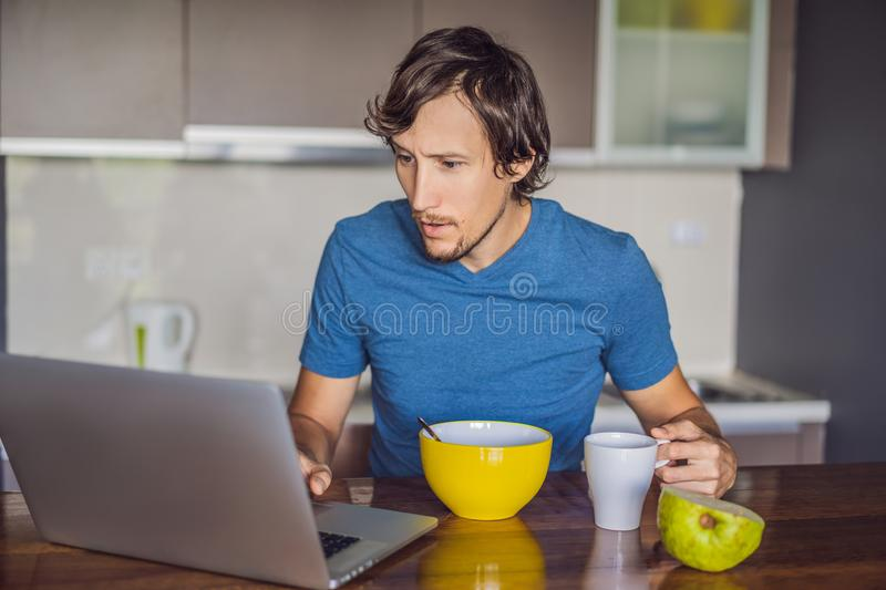 Young man having breakfast and using laptop on the kitchen royalty free stock images