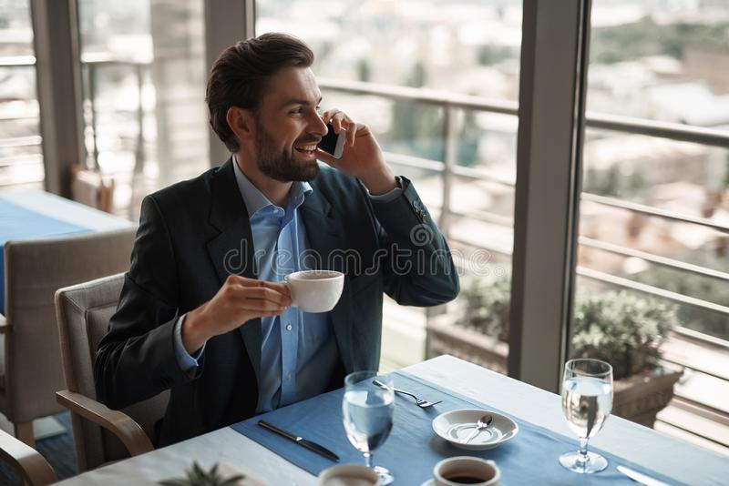 Young man having business lunch in restaurant. Concept of business lunch. Waist up portrait of young smiling businessman talking by phone while sitting in stock photo