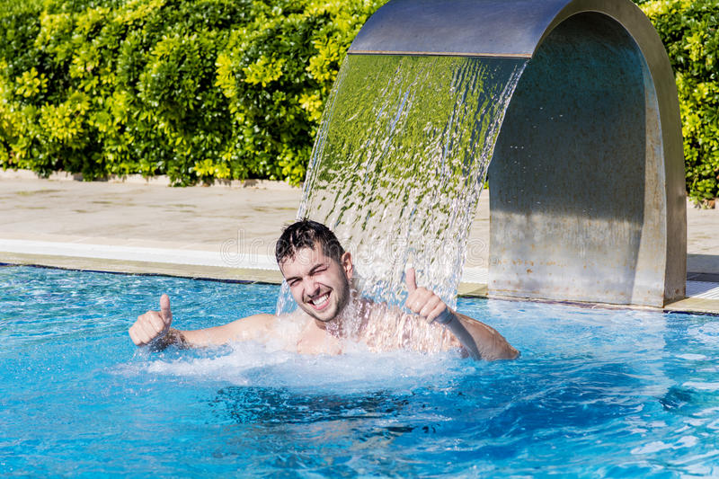 Young man having fun with the water in the swimming pool stock photos