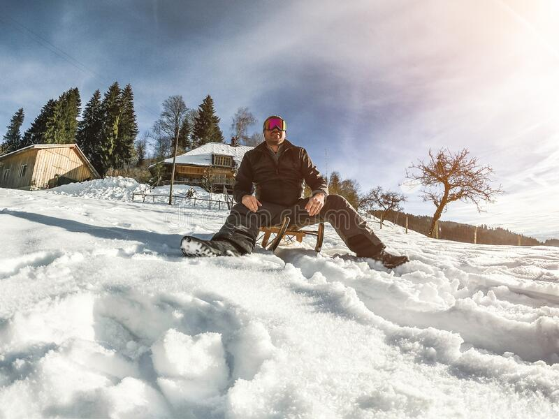 Young man having fun with wood vintage sledding on snow mountain landscape with chalet in background - Happy guy enjoy winter. Vacation - Holiday and nature stock photos