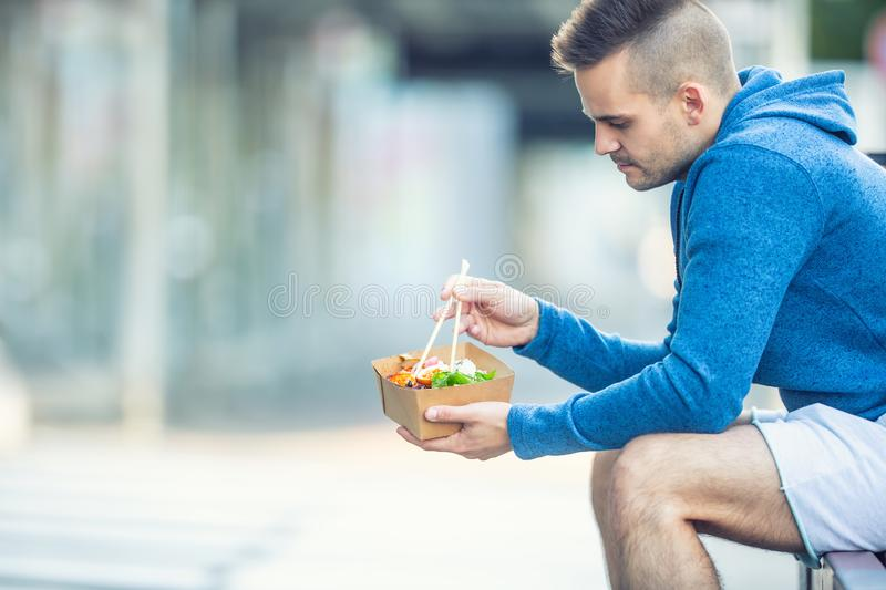Young man having lunch asian food from box of recycled paper royalty free stock photos
