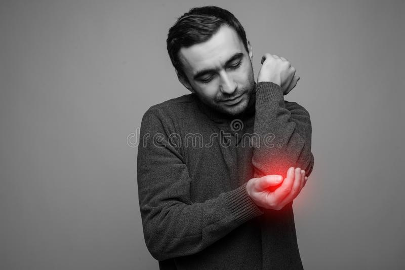 Young man having pain in his elbow - sports injury. Black and white photo with red dot royalty free stock photos