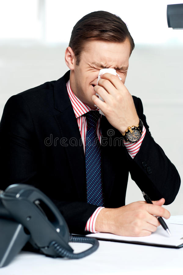 Young man having severe cold. Sneezing stock photography