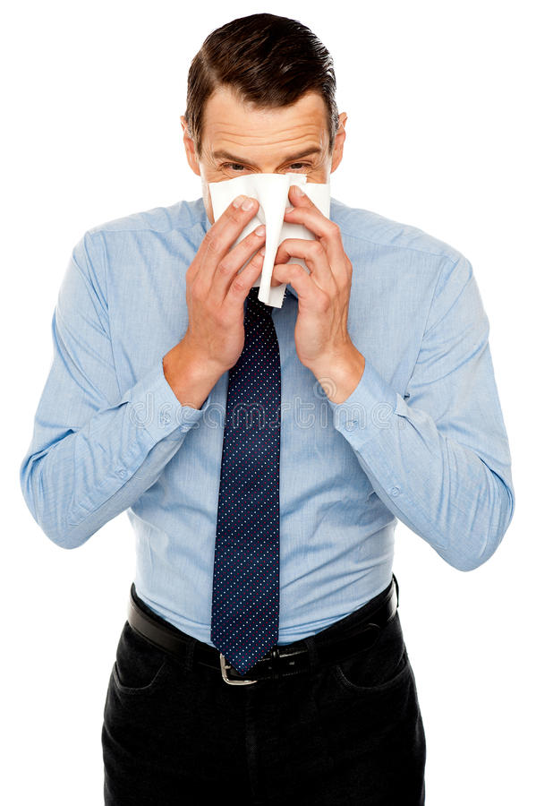 Young man having severe cold. Sneezing royalty free stock images