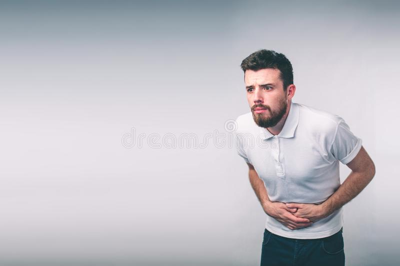 Young man having a stomachache..Close up of male body isolated on White Background. royalty free stock photos