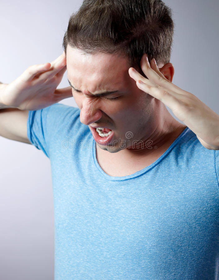 Young man with headache wearing blue shirt royalty free stock photography