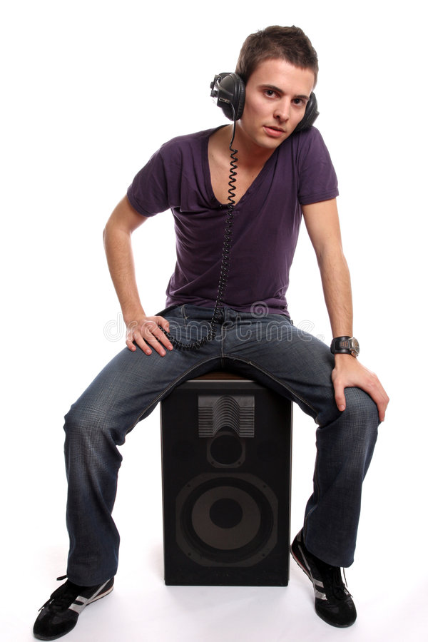Young man with headphones, seating in a speaker royalty free stock images