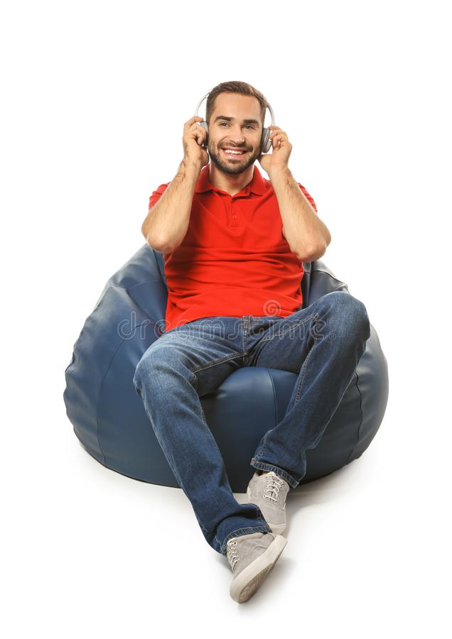 Young man with headphones sitting on beanbag chair against white background royalty free stock images