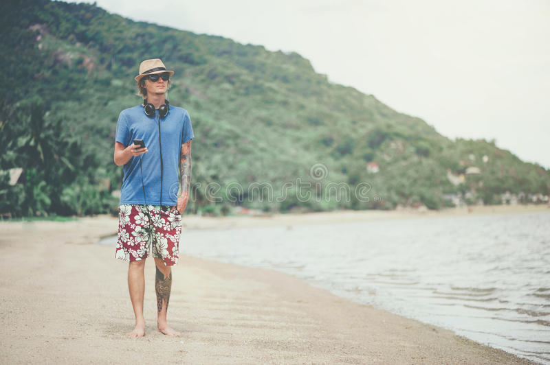 Young man in headphones and sunglasses at the beach listening to the music. Young man in headphones and sunglasses at the beach walking and listening to the stock photo