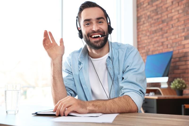 Young man with headset looking at camera and using video chat. In home office royalty free stock photography