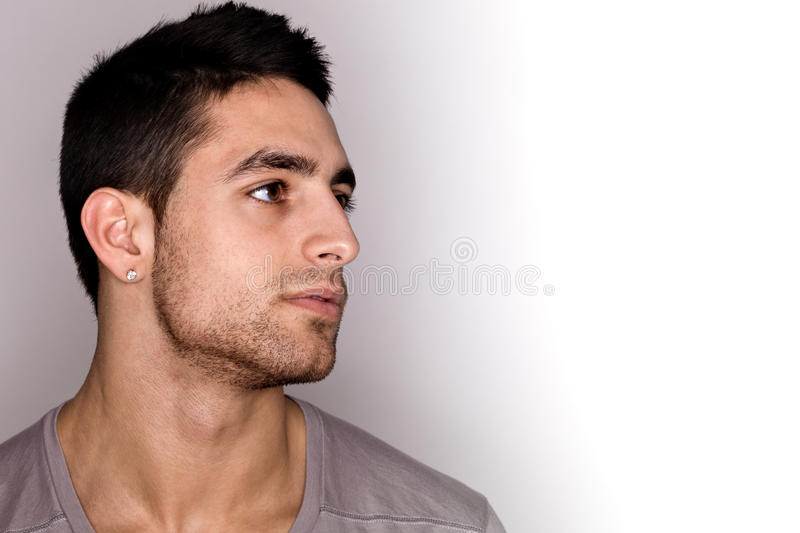 Young Man Headshot. Studio shot over grey royalty free stock image