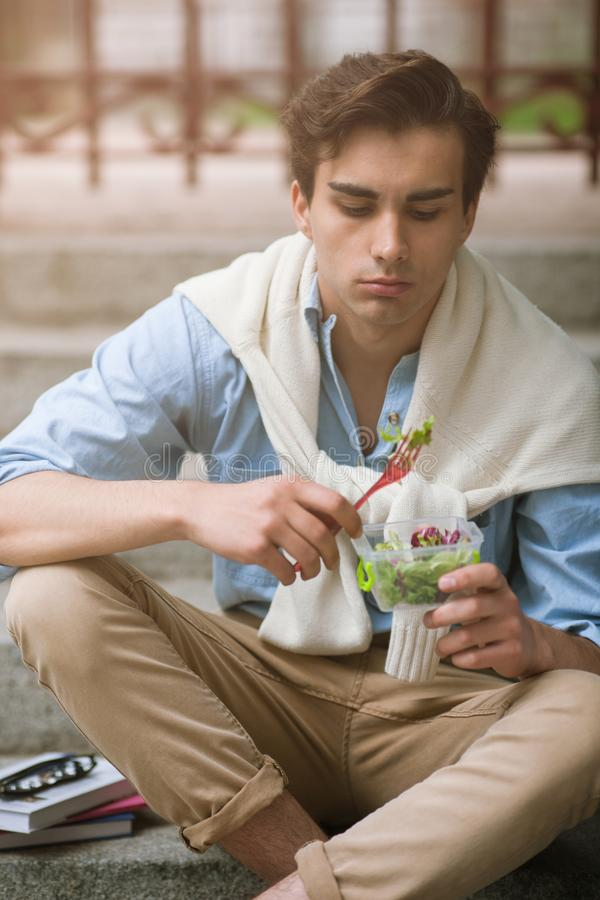 Young man with healthy food diet outdoors. Lunch break with salad, stylish male, nutrition concept royalty free stock photography
