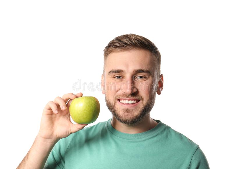 Young man with healthy teeth and apple. On white background royalty free stock images