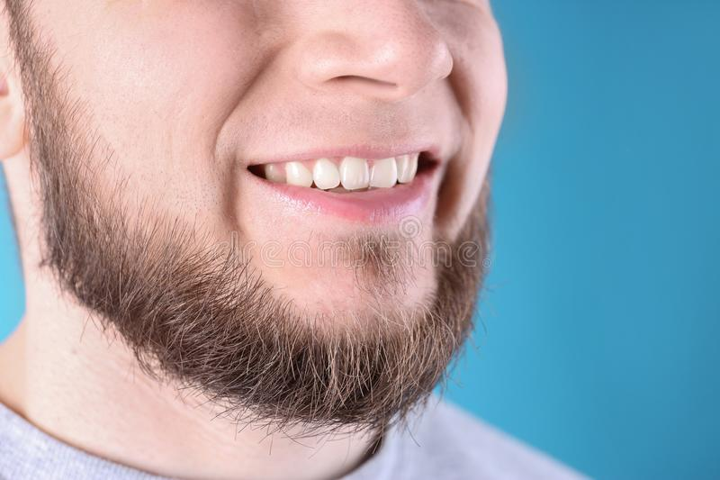 Young man with healthy teeth and beautiful smile. On color background, closeup royalty free stock photography