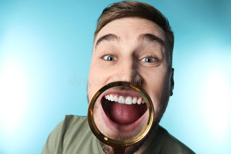 Young man with healthy teeth and magnifier. On color background stock photography