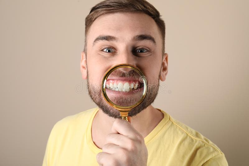 Young man with healthy teeth and magnifier. On color background royalty free stock images