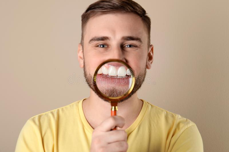 Young man with healthy teeth and magnifier. On color background royalty free stock photos