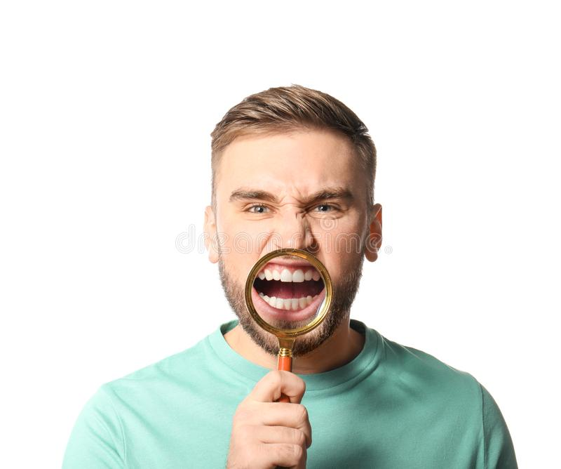 Young man with healthy teeth and magnifier. On white background royalty free stock image