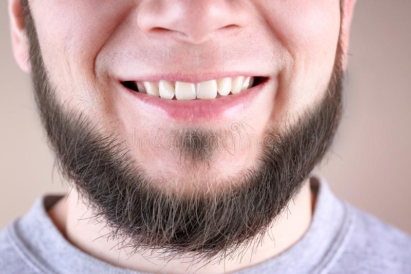 Young man with healthy teeth smiling on color background. Closeup royalty free stock photography