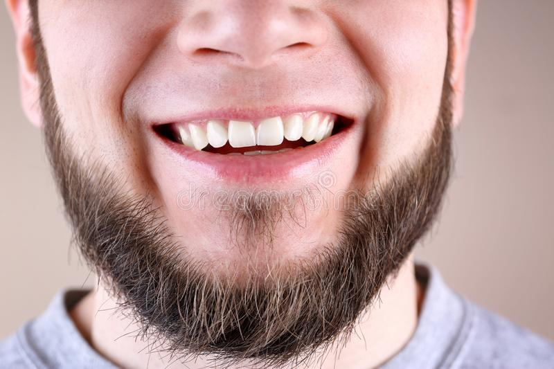 Young man with healthy teeth smiling on color background. Closeup stock photo