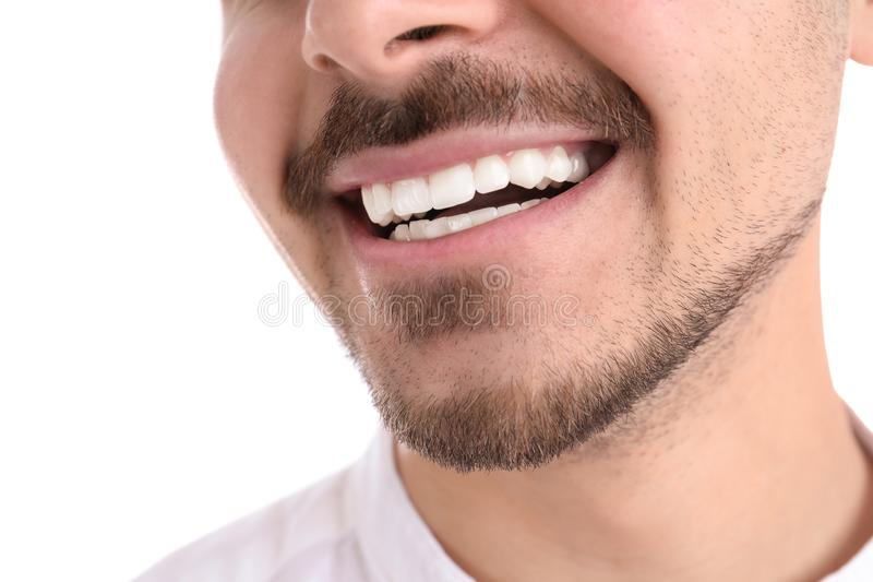 Young man with healthy teeth smiling on white background. Closeup stock photos