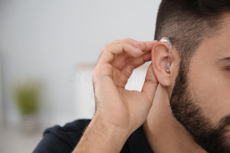 Young man with hearing aid indoors, closeup. Space for text stock photos