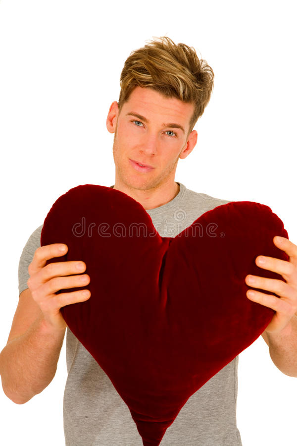 Young man with a heart shaped pillow royalty free stock photos
