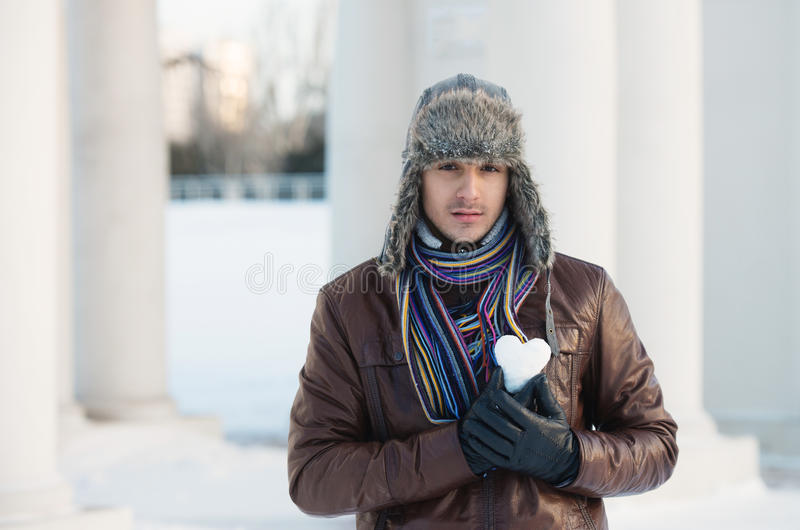 Young man with a heart shaped snowball. Portrait of a young man in an ear flap hat holding a heart shaped snowball royalty free stock image
