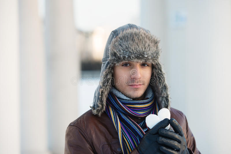 Young man with a heart shaped snowball. Portrait of a young man in an ear flap hat holding a heart shaped snowball stock photo
