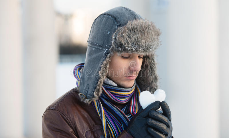 Young man with a heart shaped snowball. Portrait of a sad young man in an ear flap hat looking at the heart shaped snowball stock photos