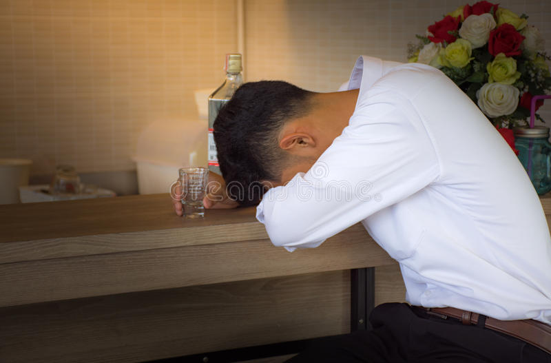 Young man heartbroken in casual clothes is sleeping near the bottle of Vodka on a bar counter in pub royalty free stock photography