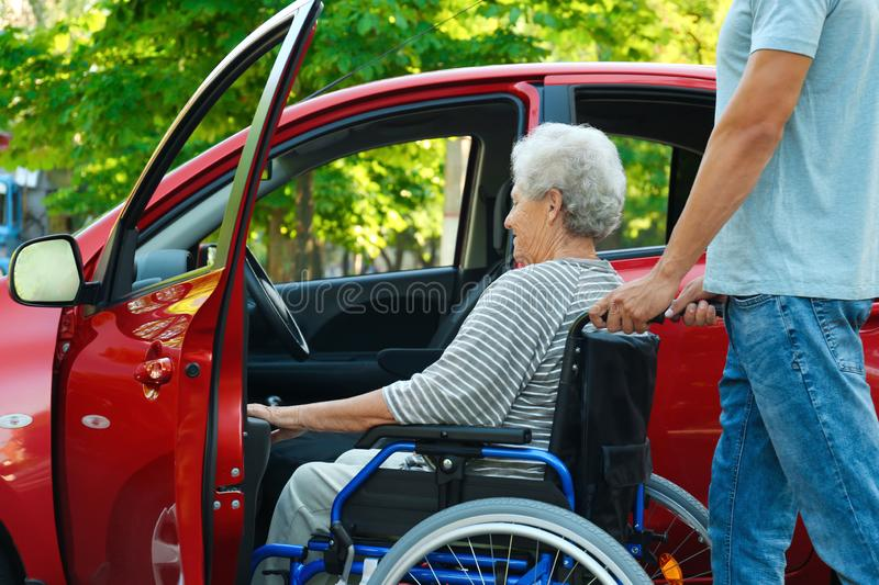 Young man helping disabled senior woman in wheelchair to get into car stock images