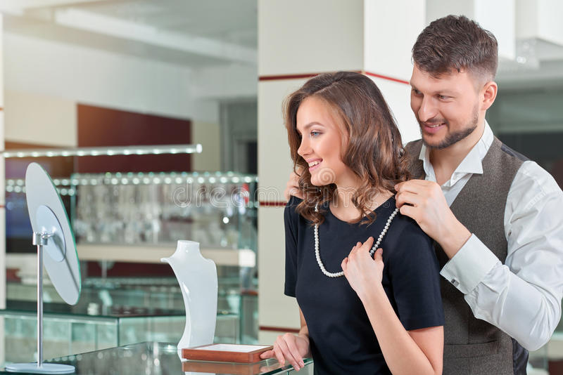 Young man helping his girlfriend with fitting necklace at the je stock photos