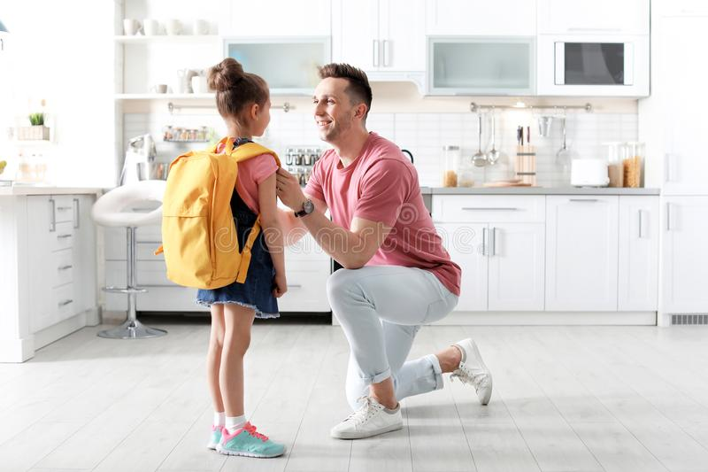 Young man helping his little child get ready for school. Young men helping his little child get ready for school at home royalty free stock image