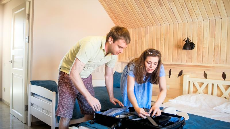 Young man helping his wife packing things and clothes in suitcase for travel trip. Man helping his wife packing things and clothes in suitcase for travel trip stock images