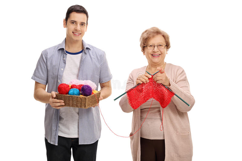 Young man helping a mature lady knit stock photos