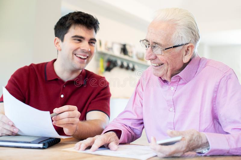 Young Man Helping Senior Neighbor With Paperwork At Home stock images