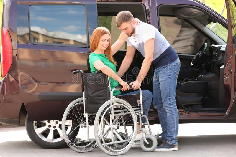 Young man helping woman to sit into wheelchair near van royalty free stock photography